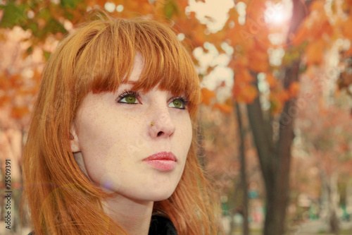 Pretty Red Hair Face With Freckles Against Autumn Folia