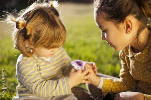Foto Niña dando flor a niña pequeña