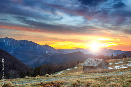 Spoed Foto op Canvas Zee zonsondergang Ramshackle chalet and beautiful sunset,Ciucas,Romania