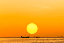 Silhouette Fishing Boat Sailing In The Sea On Sunset Background