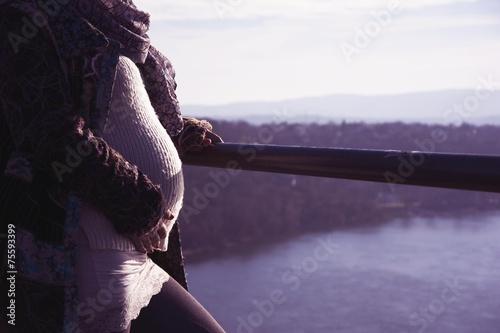 Fotografía  Mujer embarazada que se coloca en una colina que mira a través del río