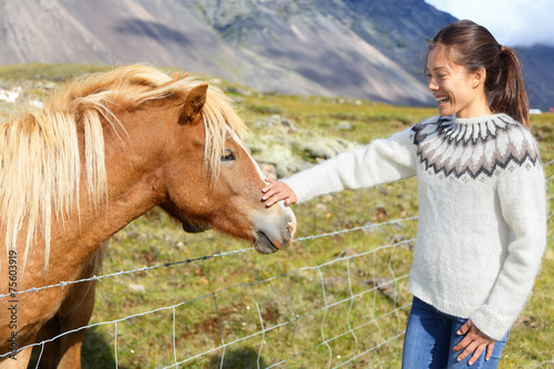 Photo  Horse - woman petting Icelandic horses in sweater