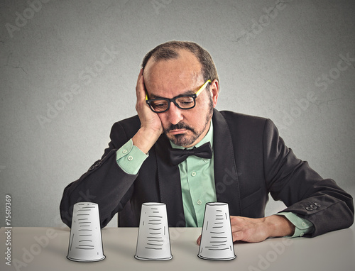 Fotografie, Obraz  Man with glasses sitting at desk playing a conjuring trick game