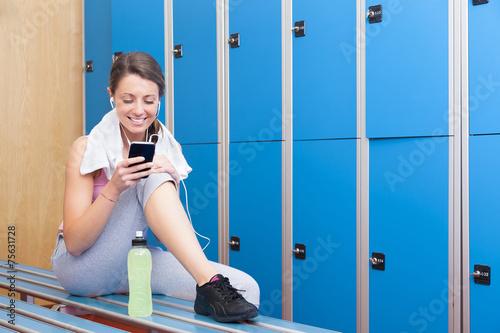 Fotografie, Obraz  Fitness smiling woman using smart phone in dressing room