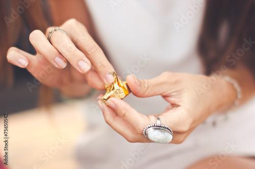 Vászonkép  Young woman hands unwrap chocolate close-up