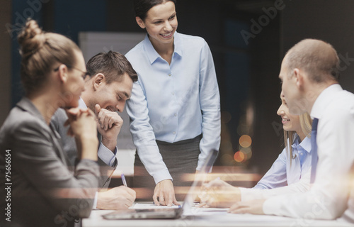Fotografiet  smiling female boss talking to business team