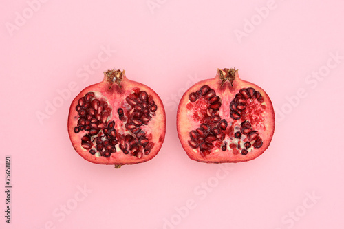 Fresh pomegranate cut in half on pink - 75658191