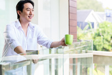 Chinese Man On Balcony Of Home With Coffee