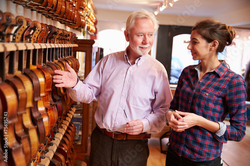 Deurstickers Muziekwinkel Salesman Advising Customer Buying Violin