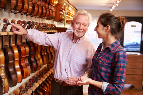 Spoed Foto op Canvas Muziekwinkel Salesman Advising Customer Buying Violin