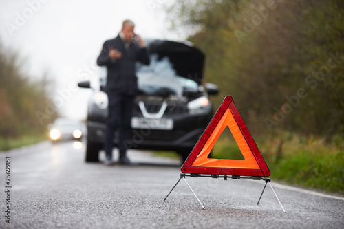 Fotografiet Motorist Broken Down On Country Road Phoning For Help