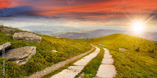 obraz PCV Droga na zboczu góry w pobliżu szczyt górski o zachodzie słońca