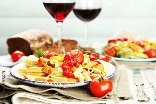 Pasta salad with vegetables and two glasses of red wine Poster