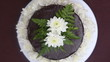 chocolate cake decorated with white fresh flower rotate on stand