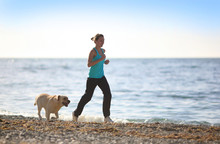 Woman Running On The Beach Wit...