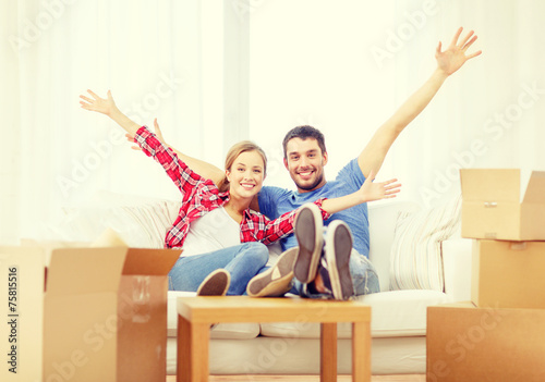 Fotografia, Obraz  smiling couple relaxing on sofa in new home
