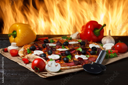 Hot pizza with oven fire on background - 75845778