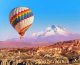 Fototapeta Sypialnia - Balloon flying over rock landscape at Cappadocia Turkey