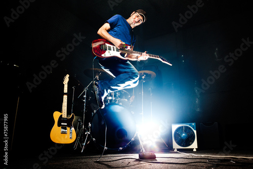 Fotografía  Live music.Rock band rehearsal.Funny time.Guitar player jumping