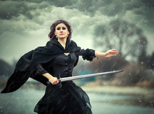 The Beautiful Gothic Girl Holds A Sword In A Hand