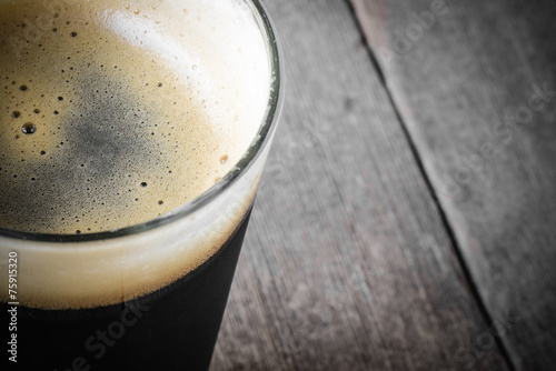 Vászonkép  Pint of Dark Beer on Wood Background