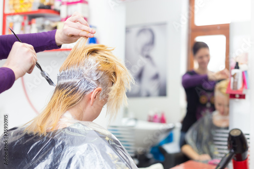 Hairdresser salon. Woman during hair dye.