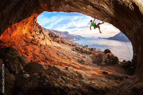 Obraz Young man lead climbing in cave before sunset - fototapety do salonu