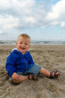toddler baby boy playing in sand on the beach