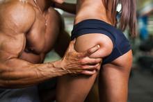 Bodybuilder Holding Girl's Pumped Buttocks