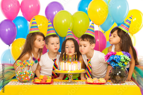 Fotografía  Kids celebrating birthday party and blowing candles on cake