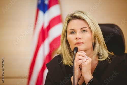 Canvas Print Portrait of a serious judge with american flag behind her
