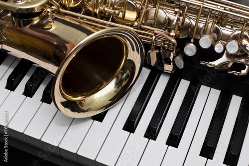 Plakat Fragment saksofonu leżącego na klawiszach fortepianu