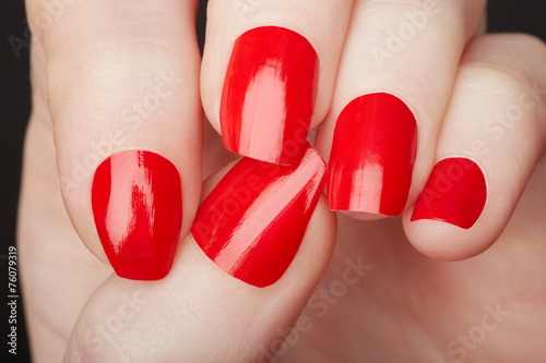 Fotografia Female hands with red nail polish close up