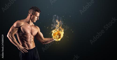 Obraz na plátne Muscular man with dumbbells on black background