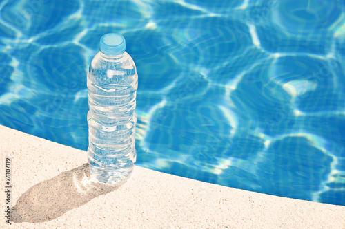Obraz na plátně  Water bottle by swimming pool