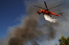 Firefigthers Are Fighting With Bushfire. Helicopter Drops Water From The Sea