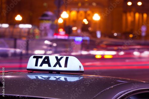 Fotografie, Obraz  Svítící nápis taxi proti projíždějících aut