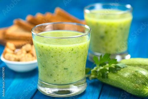 Poster Appetizer Zucchini cream soup served in glasses on blue wood