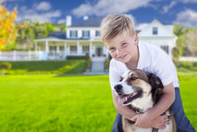 Young Boy And His Dog In Front Of House