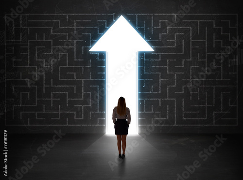 Business person looking at maze with solution arrow on the wall