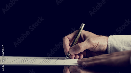 Signing a contract over dark background Canvas Print