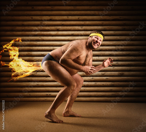 Very strange naked man farts by fire Fototapeta