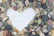 Heart Shape Made With Pebbles On A White Distressed Wood Backgro