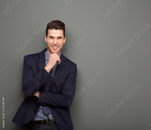 Pinturas sobre lienzo  Smiling young business man standing with hand to chin