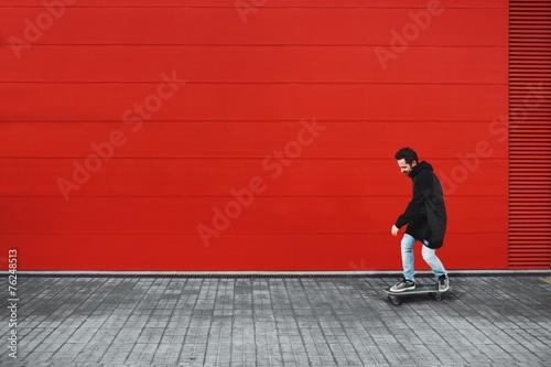 fototapeta na ścianę Facet jeździ na łyżwy z przodu czerwone ściany