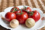 Fototapeta Fototapety do kuchni - Pomidory i cebula na talerzu na wiklinowej teksturze
