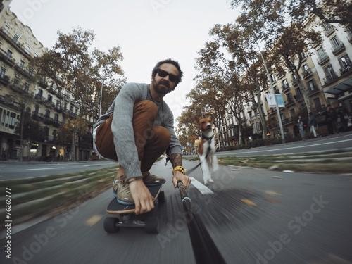Photo  Man rides his skateboard followed by his dog