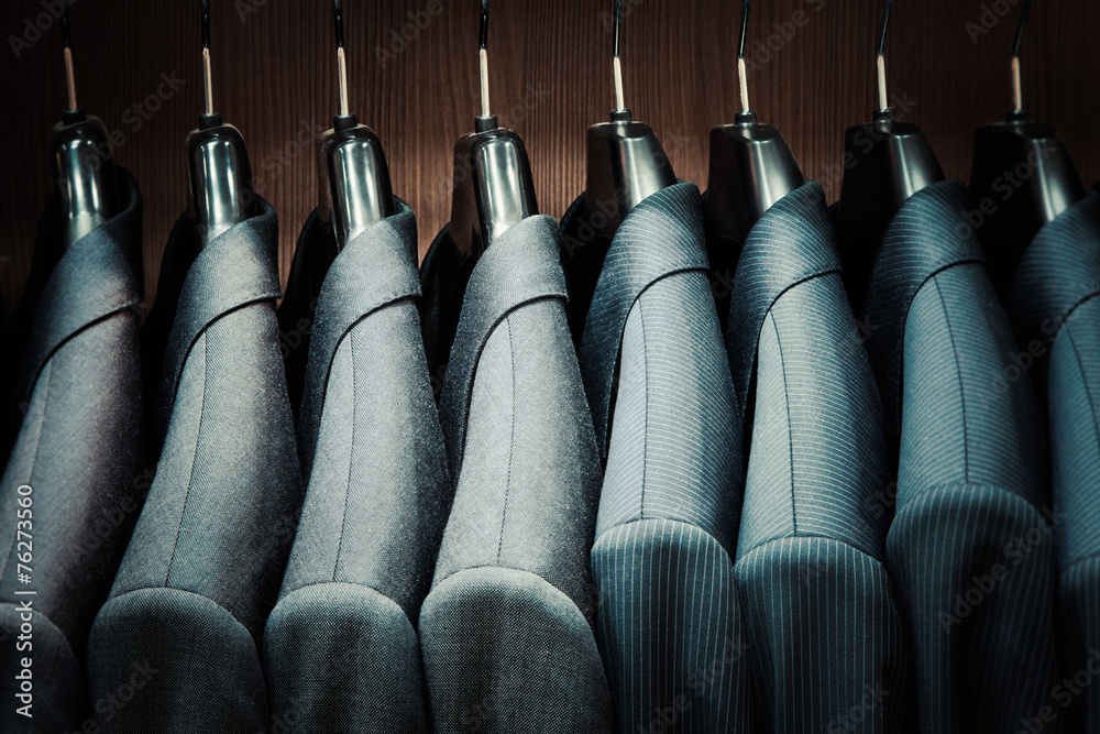 Fototapeta Row of men suit jackets on hangers