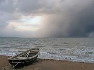 Obraz na Szkle Lonely boat on the shore of a stormy sea