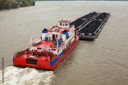 Fotografia  Tugboat Pushing a Heavy Barge